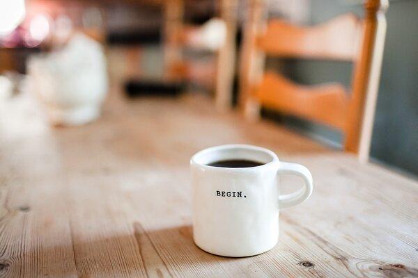 Keramik-Kaffeetasse-auf-einem-Holztisch-mit-Schriftzug-Motivation